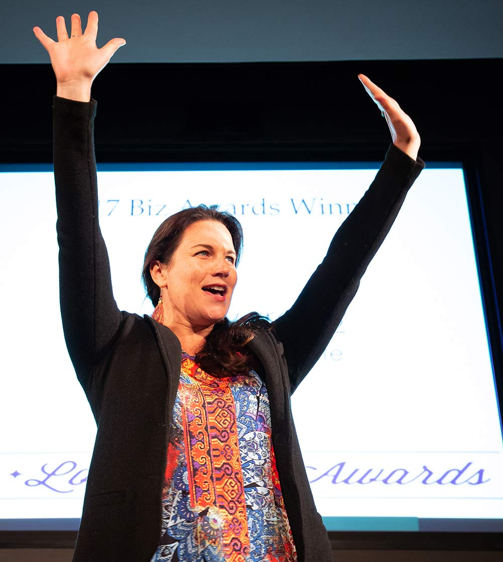 Sara Alvarado with arms in the air: Keynote Speaker | Teacher | Writer for Racial Justice
